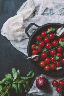 top view of cherry tomatoes, garlic and basil leaves in frying pan on gauze on wooden background