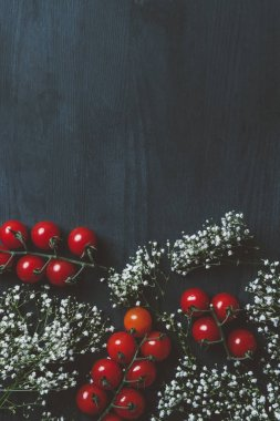 top view of ripe cherry tomatoes and white flowers on black wooden table with copy space