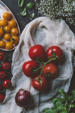 top view of red tomatoes and yellow cherry tomatoes on gauze