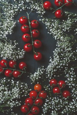 top view of red cherry tomatoes and white flowers on black wooden background