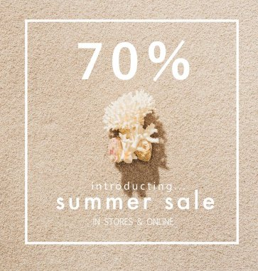 top view of coral lying on sandy beach with summer sale sign