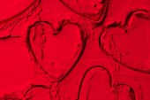 Fotografie elevated view of shapes of cookie cutters in shape of hearts on red powder