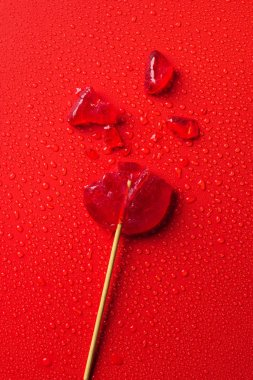 top view of broken lollipop on red surface with water drops