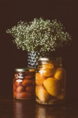 Photo glass jars with preserved tomatoes and flowers on wooden table in dark kitchen