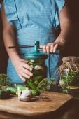 Fotografie oříznutý obraz ženy připravuje konzervované okurky v kuchyni