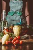 Photo cropped image of woman standing near preserved vegetables in glass jars at kitchen