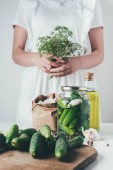 cropped image of woman preparing preserved cucumbers and holding dill at kitchen