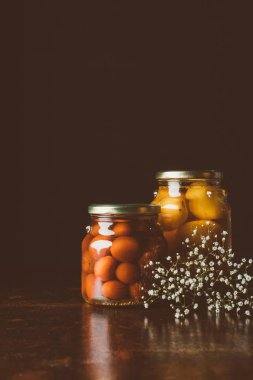 glass jars with preserved tomatoes on wooden table in dark kitchen