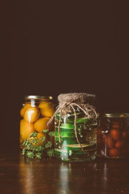 glass jars with preserved vegetables on wooden table in dark kitchen