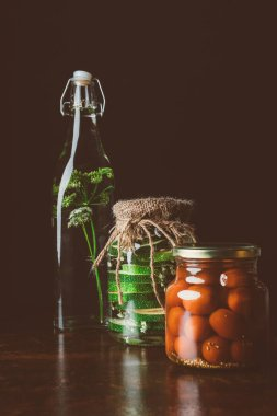 glass jars with preserved tomatoes and zucchini on wooden table in dark kitchen
