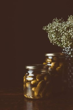 glass jars with preserved cucumbers on wooden table in dark kitchen