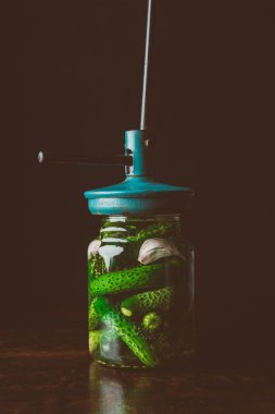 preserved cucumbers and tool on top of jar on wooden table