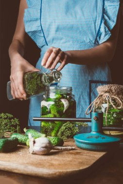 cropped image of woman preparing preserved cucumbers and pouring water into jar at kitchen