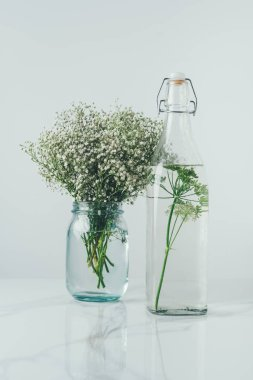 glass bottle with water and dill and glass jar with flowers on white table
