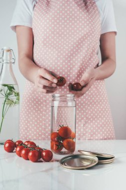 cropped image of woman putting tomatoes in glass jar at kitchen