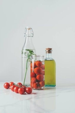 Glass jar with tomatoes, glass bottle with dill and bottle of oil on table stock vector