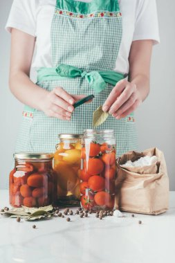 cropped image of woman adding bay leaf to preserving tomatoes at kitchen