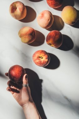 partial view of female hand and ripe peaches on light marble tabletop with shadows