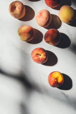 flat lay with ripe peaches on light marble tabletop with shadows