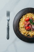 Fotografie elevated view of pasta with mint leaves, jamon and cherry tomatoes covered by parmesan on plate at marble table with fork