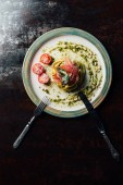 Fotografie elevated view of pasta with mint leaves, jamon, pine nuts, pesto and cherry tomatoes covered by grated parmesan on plate with fork and knife at table