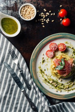 top view of pasta with mint leaves, jamon and cherry tomatoes covered by parmesan on plate at table with kitchen towel, knife, fork, pine nuts and pesto in bowl
