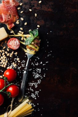 top view of fork wrapped by pasta with mint leaves, jamon, pine nuts,  and cherry tomatoes covered by grated parmesan on table surrounded by ingredients