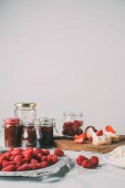 Photo selective focus of raspberries and jars with fruit jam on grey