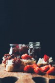 Photo selective focus of sandwiches with cream cheese, strawberry slices and fruit jam on cutting board on black