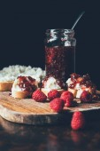 Photo selective focus of raspberries, sandwiches with fruit jam and cream cheese on cutting on black