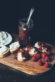 Photo elevated view of raspberries, sandwiches with fruit jam and cream cheese on cutting board on black