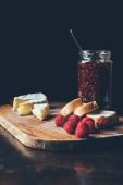 Fotografie Zavřít pohled brie, maliny, jam v jar a bagetu na prkénku u stolu