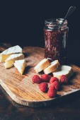 Photo selective focus of brie, raspberries, jam in jar and baguette on cutting board at table