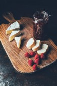 Photo elevated view of brie, raspberries, jam in jar and baguette on cutting board at table