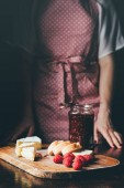 Photo cropped image of woman in apron standing near table with brie, baguette slices, raspberries and jar of jam on cutting board