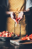 Photo partial view of woman in apron putting strawberries in jar for cooking jam
