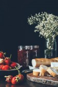 Photo close up view of strawberries, baguette, jam in jars and flowers on black