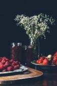 Photo selective focus of raspberries, strawberries, jars with jam and flowers on black