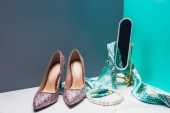 Photo toy mirror with silk scarf and high heels in miniature blue room