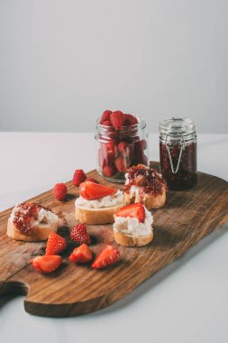 close up shot of cutting board with strawberry jam in jars and sandwiches with cream cheese and jam on grey