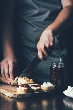 cropped image of man in apron cutting baguette for making sandwiches with cream cheese and fruit jam