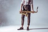 elegáns fiatal zenész, állandó és szaxofon füst a szürke gazdaságban levágott lövés