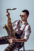 Fotografie handsome young performer in sunglasses holding saxophone and looking away on grey