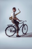 Fotografie young stylish musician in sunglasses holding saxophone and riding bicycle on grey