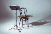 Photo music stand for notes and saxophone on chair in studio