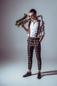 Fotografie stylish young musician in sunglasses holding saxophone and looking down on grey