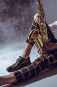 Photo partial view of stylish young musician sitting with saxophone in smoke on grey