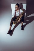 Fotografie high angle view of stylish young musician in sunglasses sitting with saxophone on grey