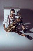 Fotografie stylish young musician in sunglasses sitting with saxophone on grey