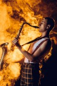 Fotografie side view of stylish professional saxophonist playing sax in smoke